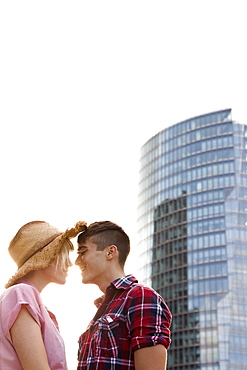 A young couple, face to face, in front of a skyscraper, berlin, germany