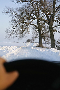View of snow covered country road through car windshield