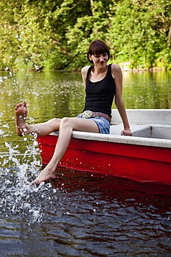 A young woman in a rowboat splashing water with her foot