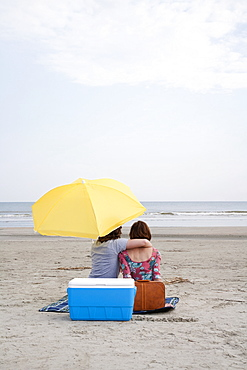 A young couple at the beach, rear view