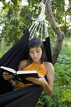 Young woman lying in hammock and reading