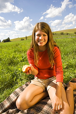Teenager eating apple in field