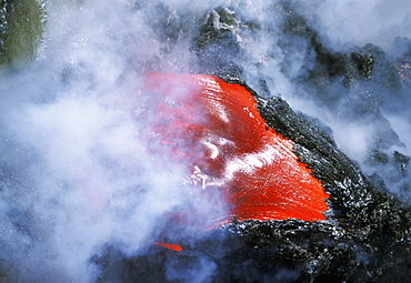 Steam rises from lava flowing into the sea, Hawaii