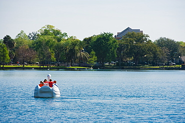 Four people on a pedal boat, Lake Eola Park, Orlando, Florida, USA