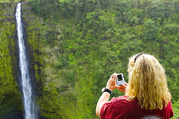 Rear view of a woman taking a photograph of a waterfall, Akaka Falls, Akaka Falls State Park, Hilo, Big Island, Hawaii Islands, USA