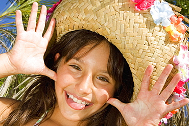 Portrait of a girl wearing a straw hat and sticking her tongue out