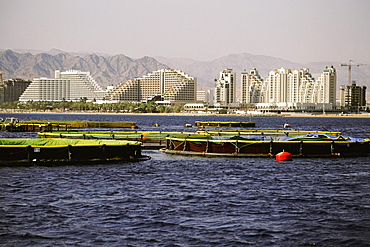 Fish farms in the sea with buildings in the background, Red Sea, Eilat, Israel