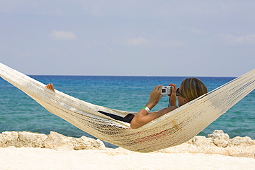 Young woman lying in a hammock and holding a digital camera, Cancun, Mexico