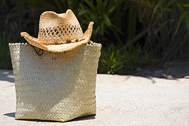 Close-up of a straw hat on a straw bag, Cancun, Mexico