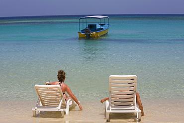 Tourists sitting on the beach chairs, West Bay Beach, Roatan, Bay Islands, Honduras