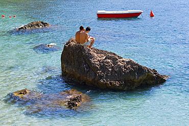 Tourists sitting on a rock, Capri, Campania, Italy