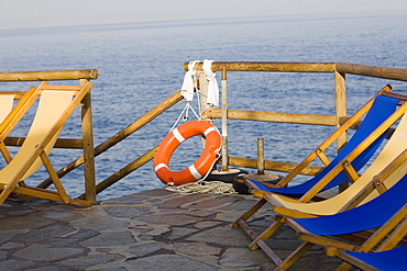 Deck chairs and a life belt on a pier, Capri, Campania, Italy