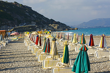 Lounge chairs and beach umbrellas on the beach, Rhodes, Dodecanese Islands, Greece