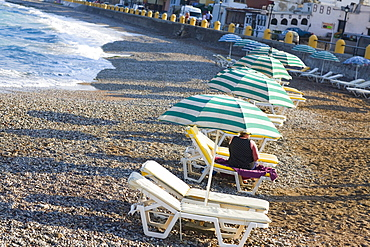 Beach umbrellas and lounge chairs on the beach, Rhodes, Dodecanese Islands, Greece