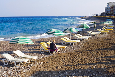 Beach umbrellas and lounge chairs on the beach, Lindos, Rhodes, Dodecanese Islands, Greece