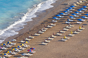 High angle view of beach umbrellas and lounge chairs on the beach, Rhodes, Dodecanese Islands, Greece