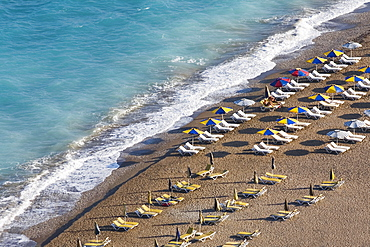 High angle view of beach umbrellas and lounge chairs on the beach, Greece