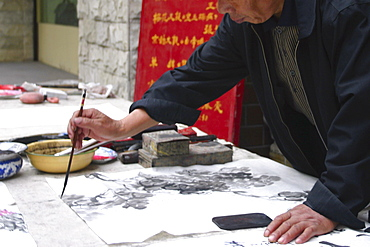 Mid section view of a man calligraphing, Beijing, China
