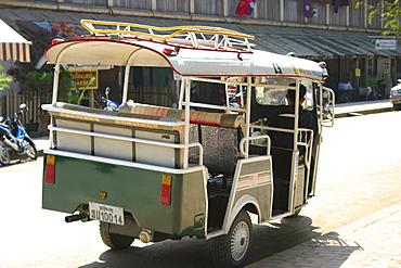 Rear view of a man driving a jinrikisha, Vientiane, Laos