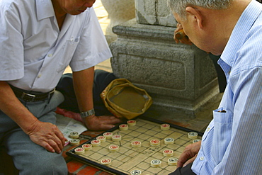 Two mature men playing a board game, Hanoi, Vietnam