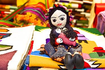 Doll and carpets in a market stall, Pisaq, Cuzco, Peru