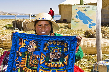Portrait of a young woman showing a decorated blanket, Peru
