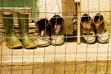 Close-up of a chain-link fence in front of shoes, Italian Riviera, Cinque Terre National Park, Vernazza, La Spezia, Liguria, Italy