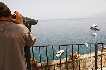 Rear view of a man looking through a coin-operated binocular, Bay of Naples, Via Aniello Califano, Sorrento, Sorrentine Peninsula, Naples Province, Campania, Italy