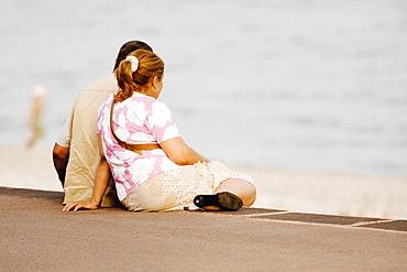 Couple sitting on the beach, Promenade Des Anglais, Nice, Provence-Alpes-Cote D'Azur, France