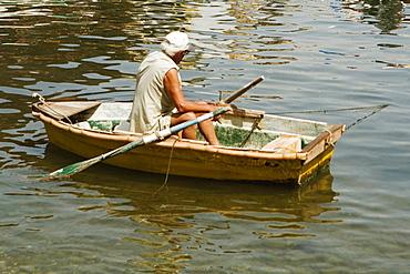 Rear view of a man sitting in a boat, Marina Grande, Capri, Sorrento, Sorrentine Peninsula, Naples Province, Campania, Italy