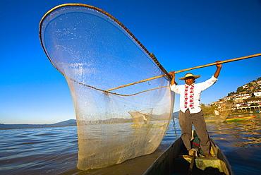 Fisherman with butterfly fishing net in a lake, Janitzio Island, Lake Patzcuaro, Patzcuaro, Michoacan State, Mexico