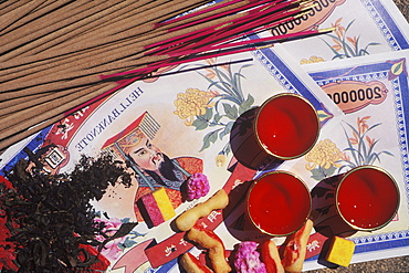 High angle view of incense sticks with bank notes and candles