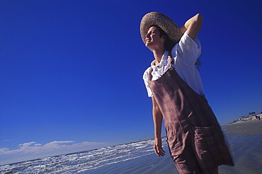 Low angle view of a young woman standing on the beach, Texas, USA