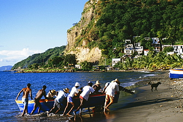 Natives pushing a boat onto a shore near the town of Castries, St. Lucia