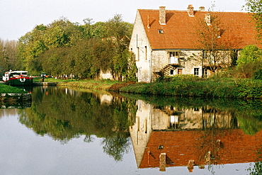 View of a barge moving upstream and passing by a farmhouse, Burgundy River, France