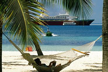 A woman relaxing on a hammock on a beach, Treasure Island, Abaco, Bahamas