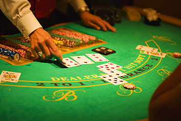 Mid section view of a casino dealer holding a playing card, Las Vegas, Nevada, USA