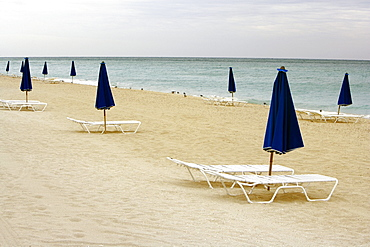 Empty lounge chair and a folded beach umbrella on the beach