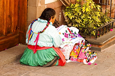 Rear view of a woman with puppets, Mexico