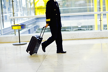 Side profile of a pilot pulling luggage at an airport, Madrid, Spain