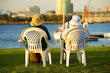 Rear view of two people sitting on a waterfront, San Diego Bay, San Diego, California, USA