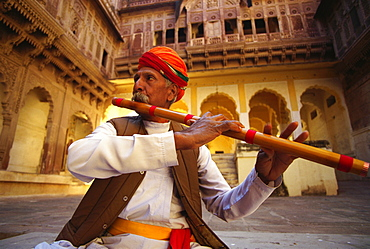 Close-up of a mature man playing a flute in a fort, Meherangarh Fort, Jodhpur, Rajasthan, India