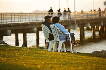 Side profile of two people sitting on a waterfront, San Diego Bay, San Diego, California, USA