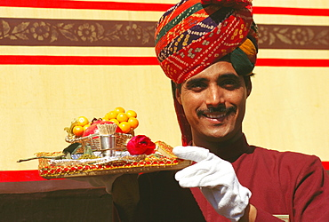 Portrait of a train steward holding winter cherries and a Rose flower on a serving tray, India