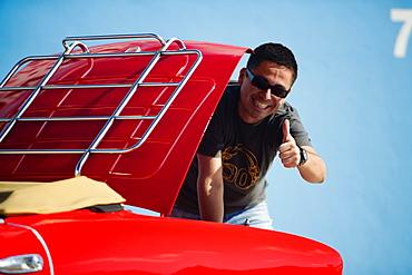 Mid adult man standing behind a convertible car, Miami, Florida, USA