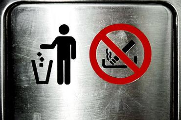 Close-up of Trash and No Smoking sign on a metal door