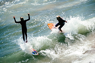 High angle view of two boogie boarders on the beach