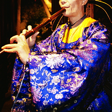 Mid section view of a woman blowing flute, Suzhou, China