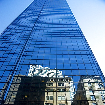 Low angle view of the reflection of buildings on a glass front, John Hancock tower, Boston, Massachusetts, USA