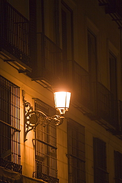 Lantern on a building lit up at night, Madrid, Spain